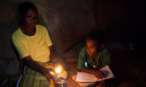 A mother lights a small lamp for her child to study by in Masaka, Uganda, East Africa
