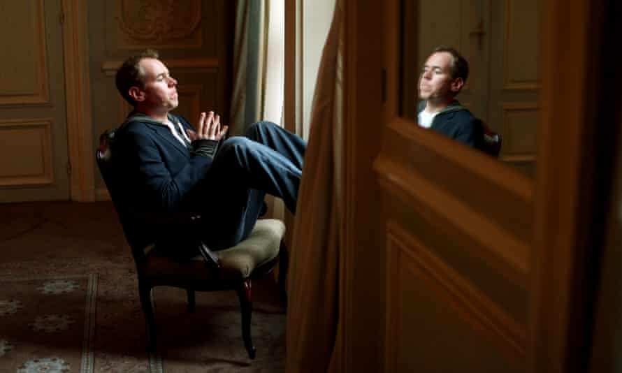 Bret Easton Ellis sits in a chair by a window, his feet perched in the window ledge