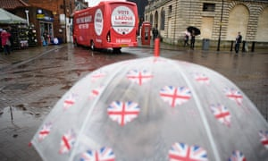 A woman shelters under as the Labour battlebus arrives in Lincoln, England.