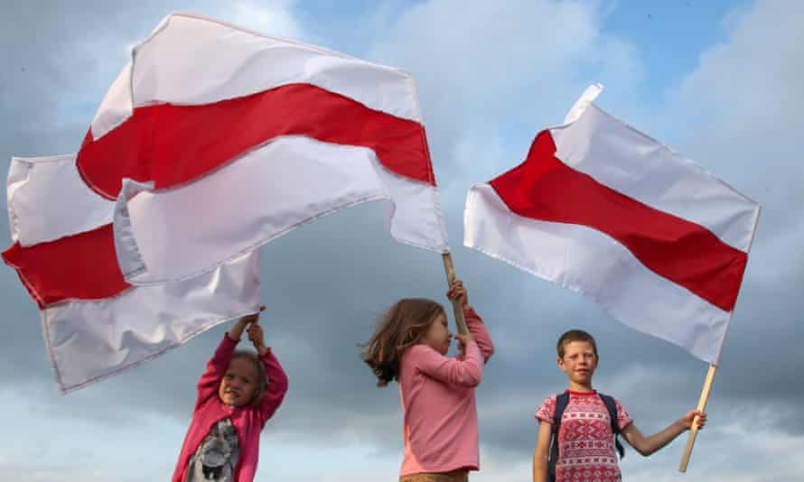 Children wave Belarus's traditional red and white flag.