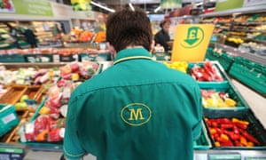 A Morrisons employee replenishes the produce aisle