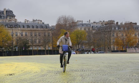 A man rides his bicycle on yellow paint poured on the street during a protest by activists from environmental group Greenpeace on the Champs-Elysee in Paris, ON Friday.