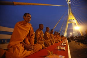 Bangkok, Thailand Buddhist monks sit at King Bhumibol bridge in as they wait for mourners to offer food on the birthday of the late King Bhumibol Adulyadej