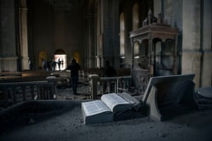 A Bible lies open on an altar as journalists report  inside the damaged Ghazanchetsots Cathedral in the historic city of Shusha, near the capital of the disputed Nagorno-Karabakh province.