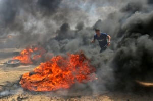 A Palestinian man uses the smoke from burning tyres for cover near Khan Yunis