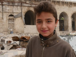 Fourtenn-year-old Yamin Saeed hangs out with his friends in the ruins.