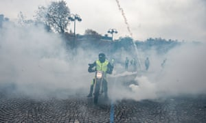 A motorcyclist with a Guy Fawkes mask drives amid teargas near the Champs-Élysées in Paris