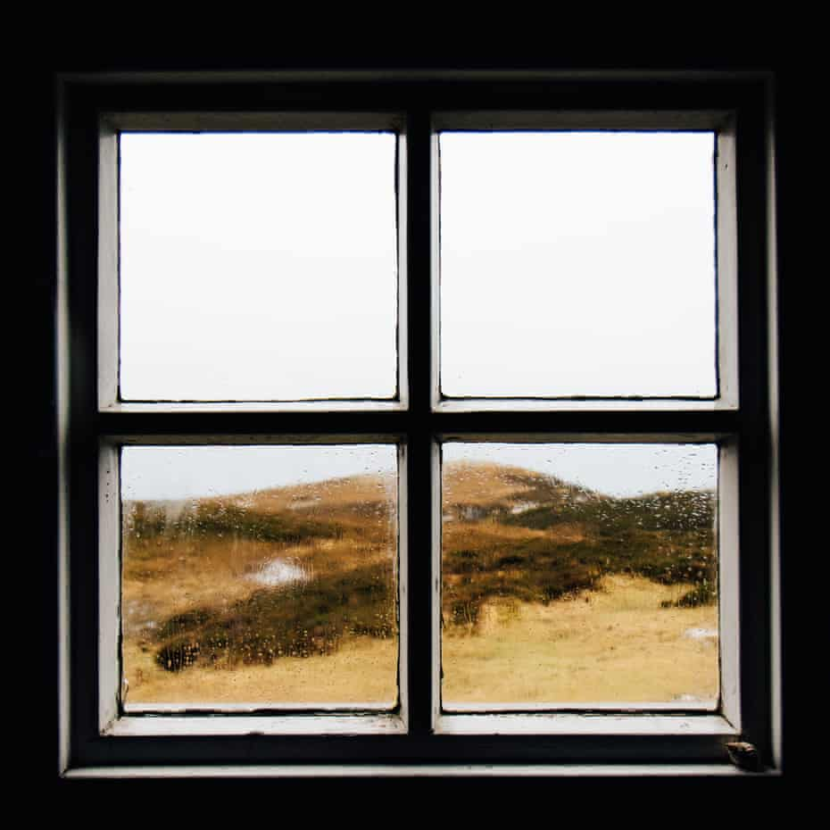 Viewed from indoors, raindrops on a bothy window.