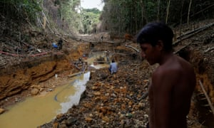 A Yanomami indian follows agents of Brazil's environmental agency in a gold mine during an operation against illegal gold mining on indigenous land, in Roraima state, Brazil, in 2016.