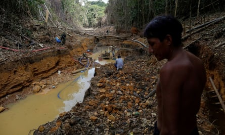 A Yanomami person follows agents of Brazil's environmental agency in a gold mine in the Amazon rainforest, in Roraima state, Brazil, on 17 April 2016.
