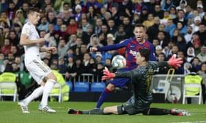 Real Madrid's goalkeeper Thibaut Courtois, right, blocks a shot of Barcelona's Arthur.