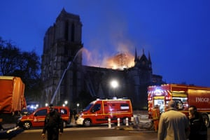 French firemen try to extinguish a fire as flames are burning the roof of the Notre-Dame Cathedral in Paris