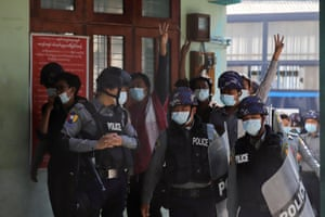Protesters salute as they arrive at a court in Mandalay
