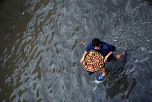A man carries a basket with wild mushrooms as he walks on a flooded street after a rainstorm in Kunming, China