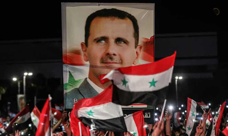 Syrians wave national flags and carry a large portrait of Bashar al-Assad after elections in May
