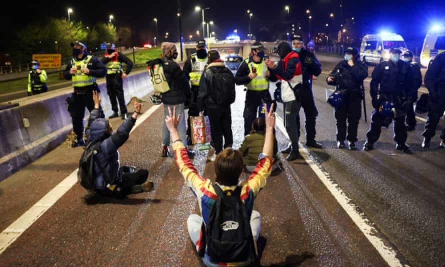 Police officers stand guard as demonstrators block the M32 motorway during a 'kill the bill' protest in Bristol