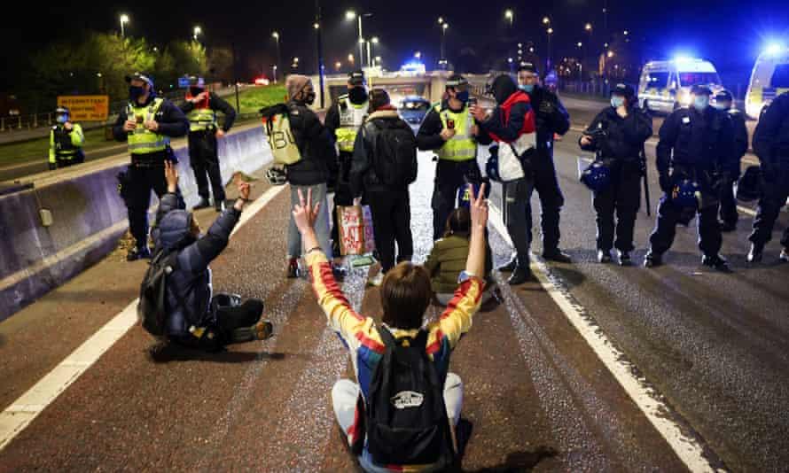 مأموران پلیس در حالی که تظاهرکنندگان در اعتراض به