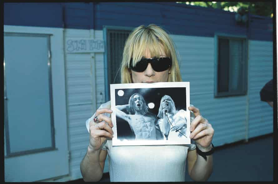 Kim Gordon holding an image of herself and Iggy Pop.