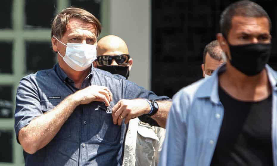 Brazil's president, Jair Bolsonaro (left), leaves after voting during municipal elections in Rio de Janeiro.