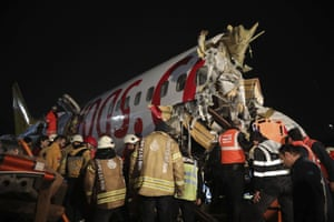 Emergency personnel work around the wreckage of an aircraft after it skidded off the runway as it tried to land in bad weather at Sabiha Gokcen Airport.