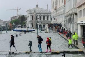 People walk on a footbridge in the flooded Riva degli Schiavoni during a high-water (Acqua Alta) alert in Venice