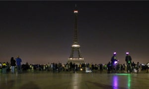 People gather at Trocadero plaza as the lights of the Eiffel tower falls dark at midnight in Paris, France, Wednesday May 24, 2017. Paris mayor Anne Hidalgo says the Eiffel Tower will fall dark overnight to honor the victims of the suicide attack at an Ariana Grande concert in Manchester that left 22 people dead as it ended on Monday night. (AP Photo/Francois Mori)