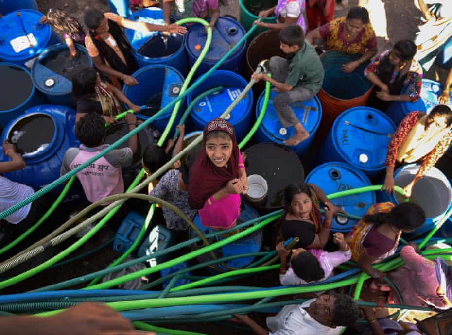 Villagers scramble around a tanker for drinking water, in Latur, India