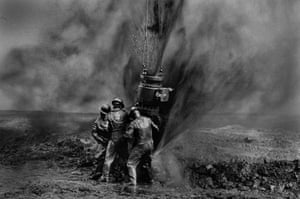 Workers struggle to fix a damaged oil well after Saddam Hussein's forces set hundreds alight during the Gulf war. Kuwait, April 1991