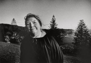 woman in loose blouse in front of tall pine trees