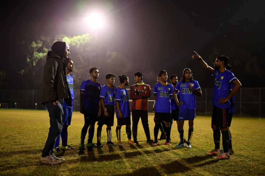 Mohammad Aiyas (right), a former refugee and captain of QR The Brave FC, talks to his players at half-time.