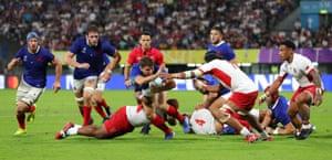 Antoine Dupont of France looks to evade Zane Kapeli of Tonga.
