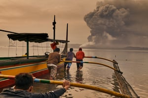 Residents prepare their boats to evacuate while the volcano erupts