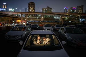 A couple cocooned in their car at a drive-in cinema in Seoul.