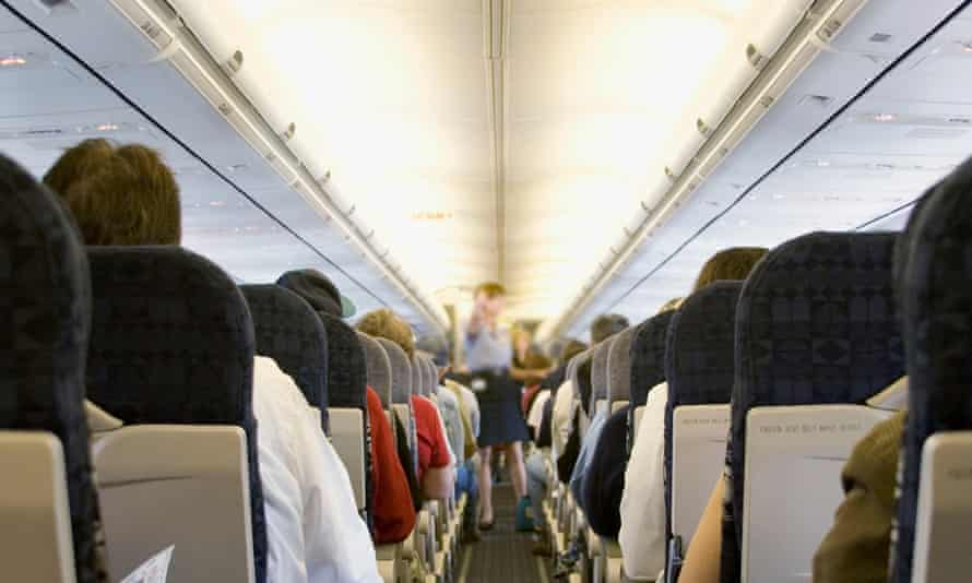 Airplane aisle: Passengers on a commercial flight with attendant