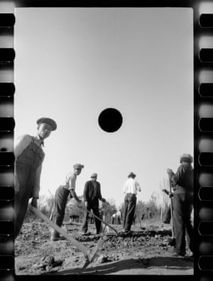 Group of men raking earth, with black circle in sky above them