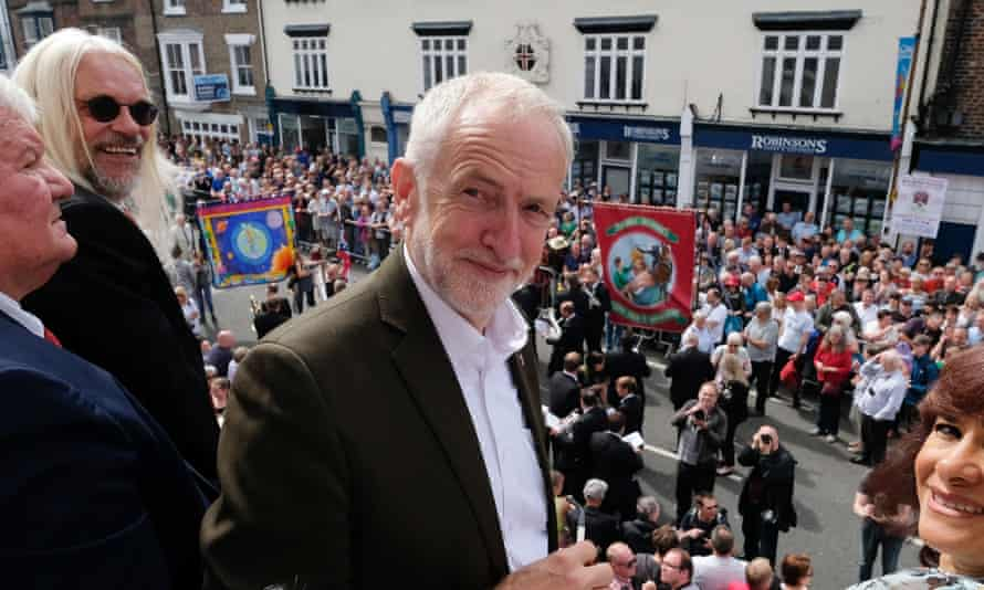 Labour leader Jeremy Corbyn stands on the balcony of the County Hotel as colliery bands play below during the 135th Durham Miners Gala on 13 July in Durham, England.