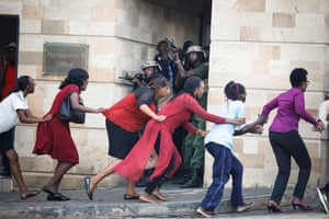 Women are evacuated as security forces search for the perpetrators of an attack at a Nairobi hotel and office complex.