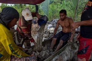 Family members break up the mud using their feet and hands in their search for gold