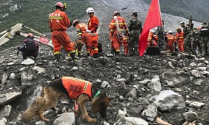 Rescuers with sniffer dogs stand near earthmoving equipment digging at the site of a landslide in Xinmo village in Maoxian County in southwestern China's Sichuan Province.