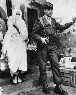 "The Observer's front page photograph on 14 January 1962. The caption read: ""In Algiers, city of violence, a woman shops in the Casbah, a soldier keeps watch. Fourteen people, 11 of them Muslims, died and 45 were wounded in knife, gun and grenade attacks throughout Algeria yesterday."""