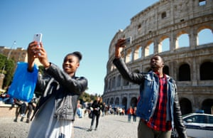 Tourists take selfies in front of the Colosseum in Rome