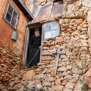 Ο πατέρας Αρσένιος από την είσοδο της κυψέλης του.  Δεν έχει αφήσει εκεί για 64 χρόνια, καθώς είναι πάρα πολύ ηλικιωμένος και ευπαθής τώρα για να ανεβεί στα βράχια που περιβάλλουν την κυψέλη του.