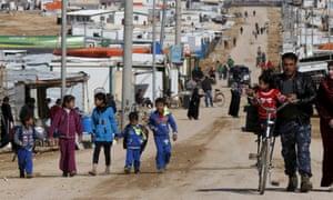Syrian refugees walk at Zaatari refugee camp in Jordan.
