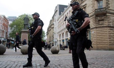 Armed police patrol the streets Of Manchester.