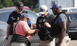 A registered immigrant shows federal agents his identification as he prepares to leave a food plant in wake of last week's immigration raids in Mississippi.