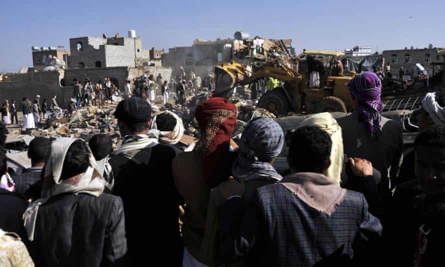 People gather at a bombed site in Sana'a after Saudi-led air strikes