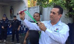 Alvarado's mayor, Bogar Ruiz Rosa, holds a slingshot. He has called the disarmament of the force a political vendetta.