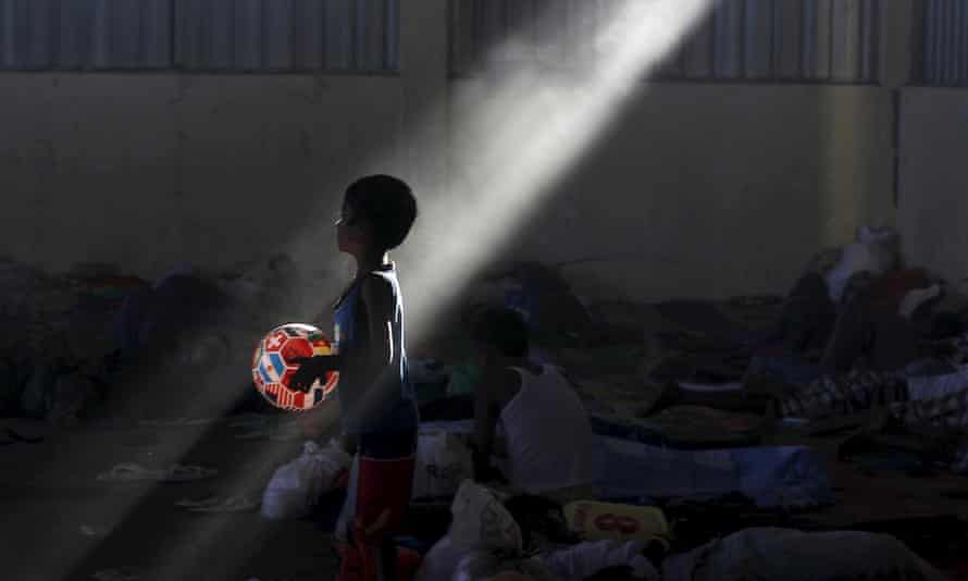 A Rohingya boy who recently arrived in Indonesia holds a ball adorned in international flags at a shelter in Kuala Langsa.