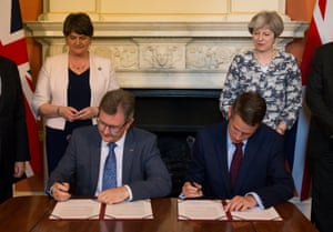 DUP leader Arlene Foster and May watch as DUP MP Jeffrey Donaldson, left, signs paperwork with Britain's Parliamentary Secretary to the Treasury, and Chief Whip, Gavin Williamson to secure a deal to govern together