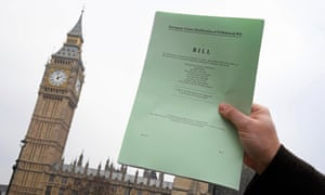 A journalist poses with a copy of the Brexit bill